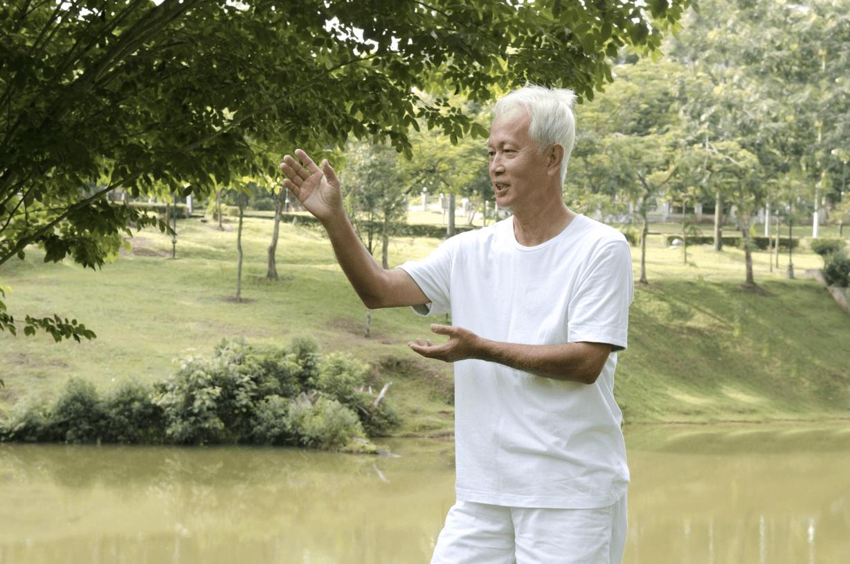 Homme mature faisant du qi gong dans un parc