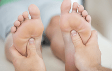 Zoom sur des mains massant des pieds, représentant la réflexologie